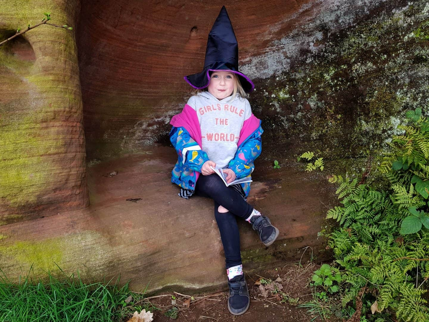 Kinver Edge and the Rock Houses National Trust West Midlands girl sat in cave wearing witches hat