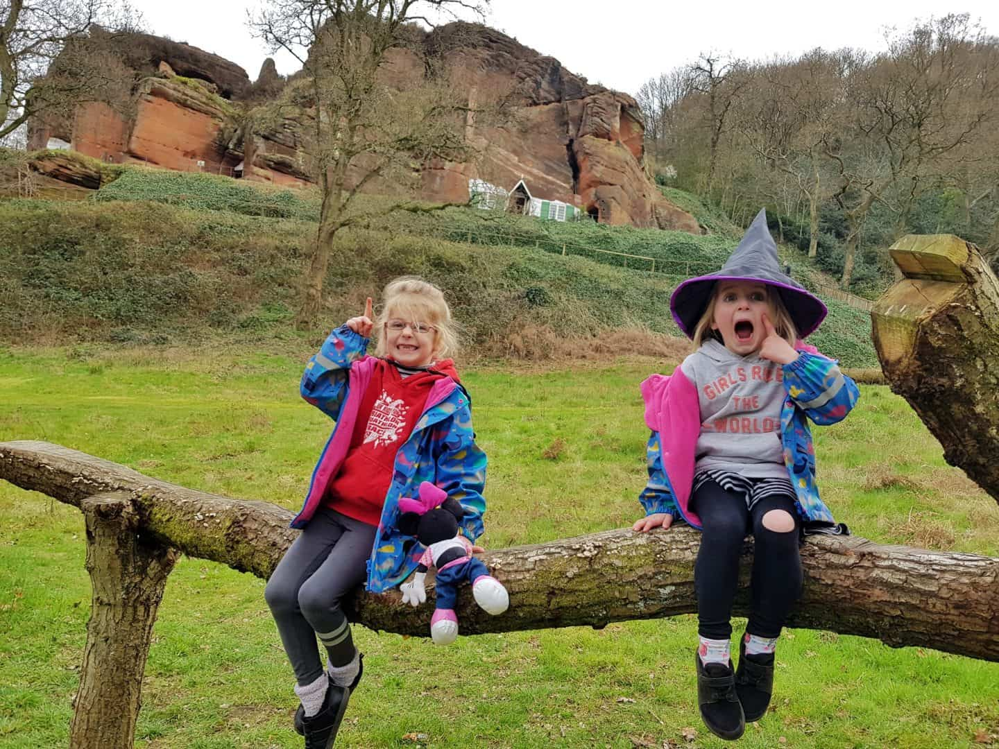 Kinver Edge and the Rock Houses National Trust West Midlands girls playing on log below rock houses
