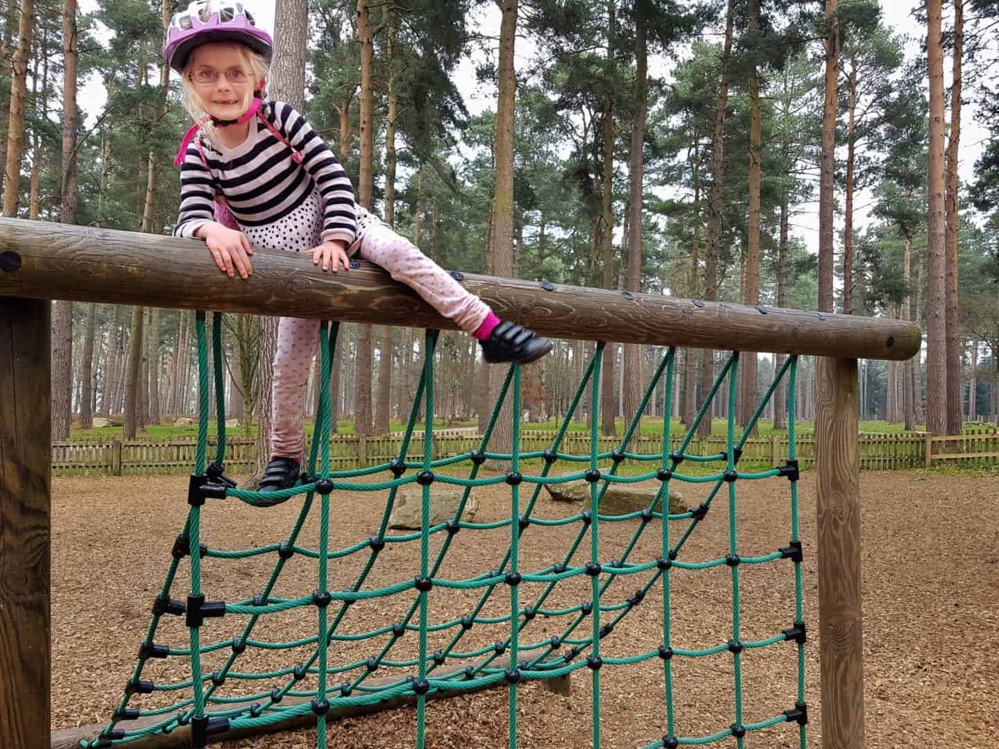 girl climbing large net in playground