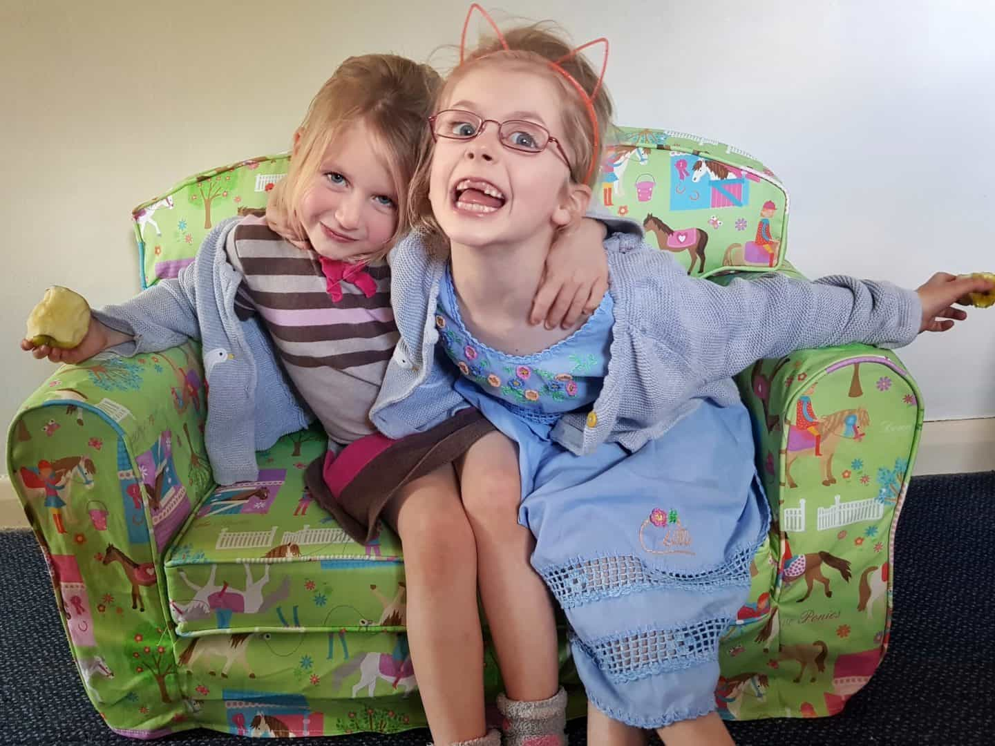 Two girls sitting on Just4Kids green loose cover sofa
