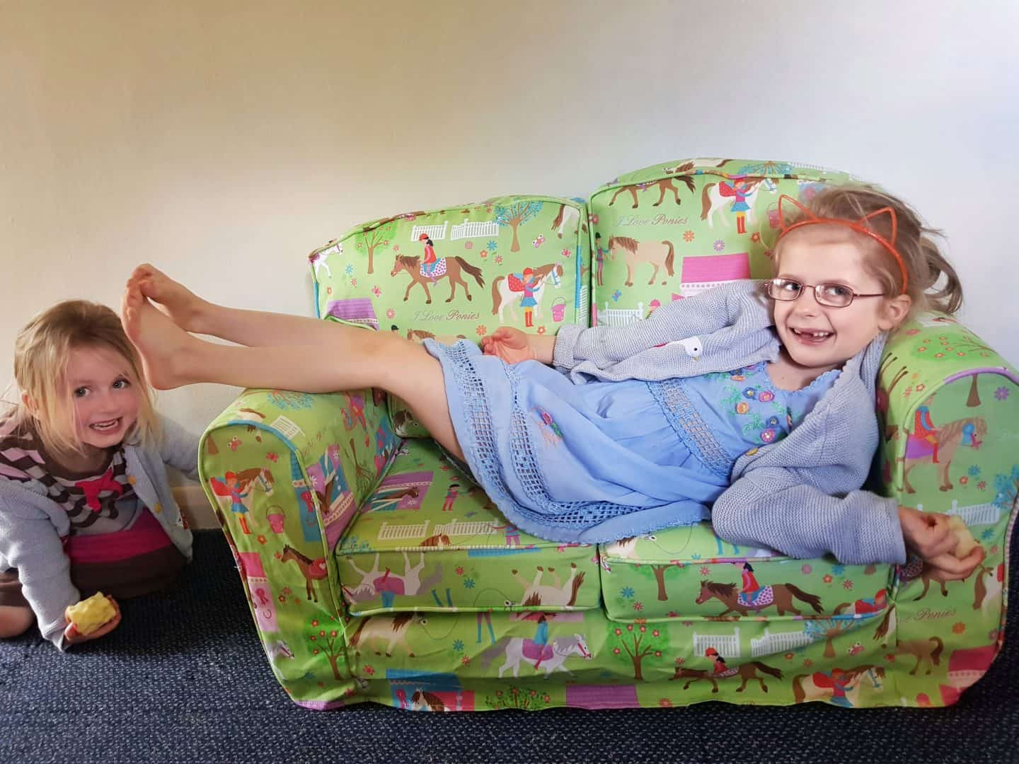 Girl lying on Just4Kids green loose cover sofa