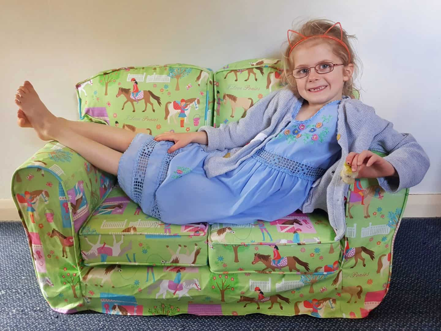 Girl sitting on Just4Kids green loose cover sofa smiling