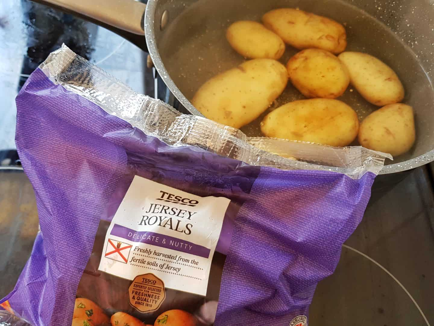 Jersey Royal New Potatoes in packaging next to pan containing potatoes