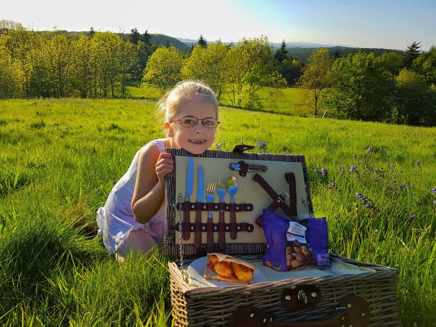 Girl behind picnic hamper on hillside with bag of Jersey Royal New Potatoes and sandwich in picnic hamper
