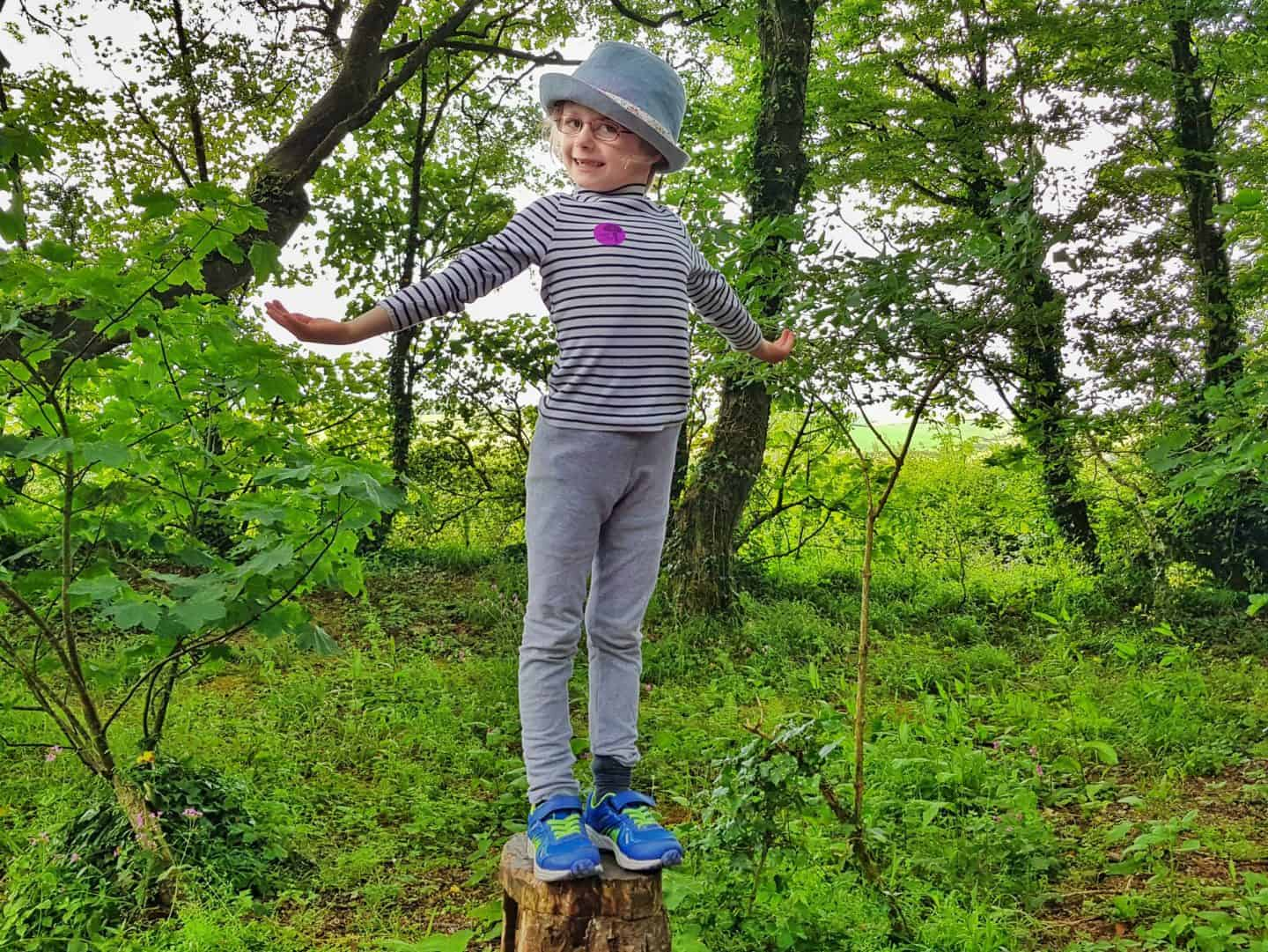 Girl in a blue hat standing on top of a log