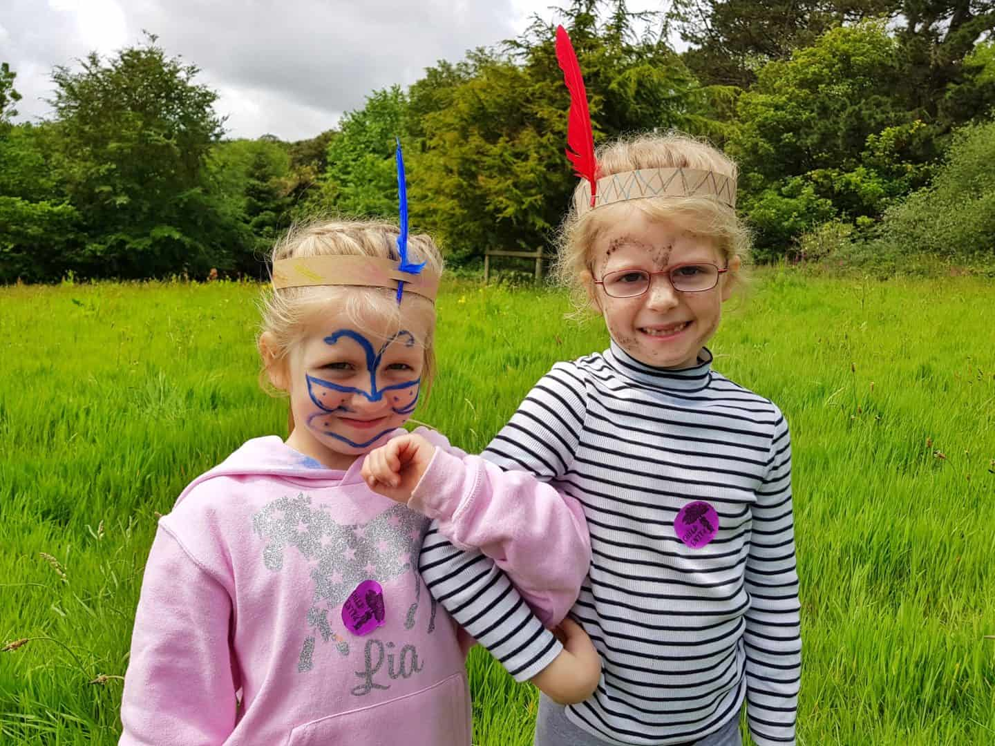Two girls with face paints and headdresses on