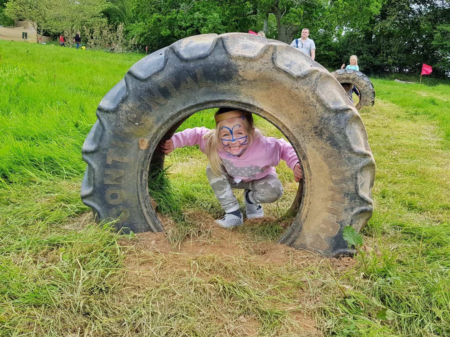 Girl wearing face paints climbing through large tyre