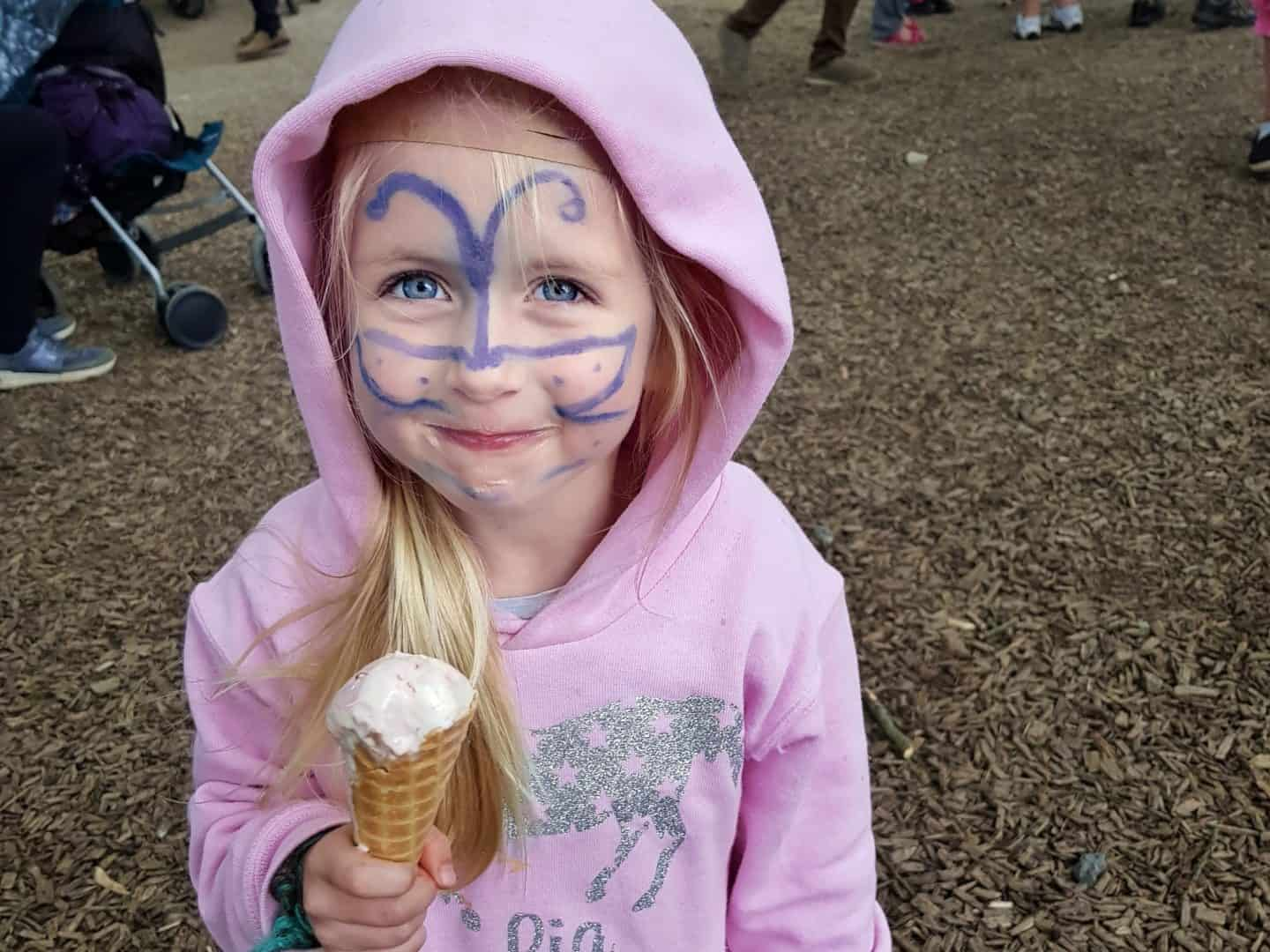 girl with blue butterfly face paint holding ice cream