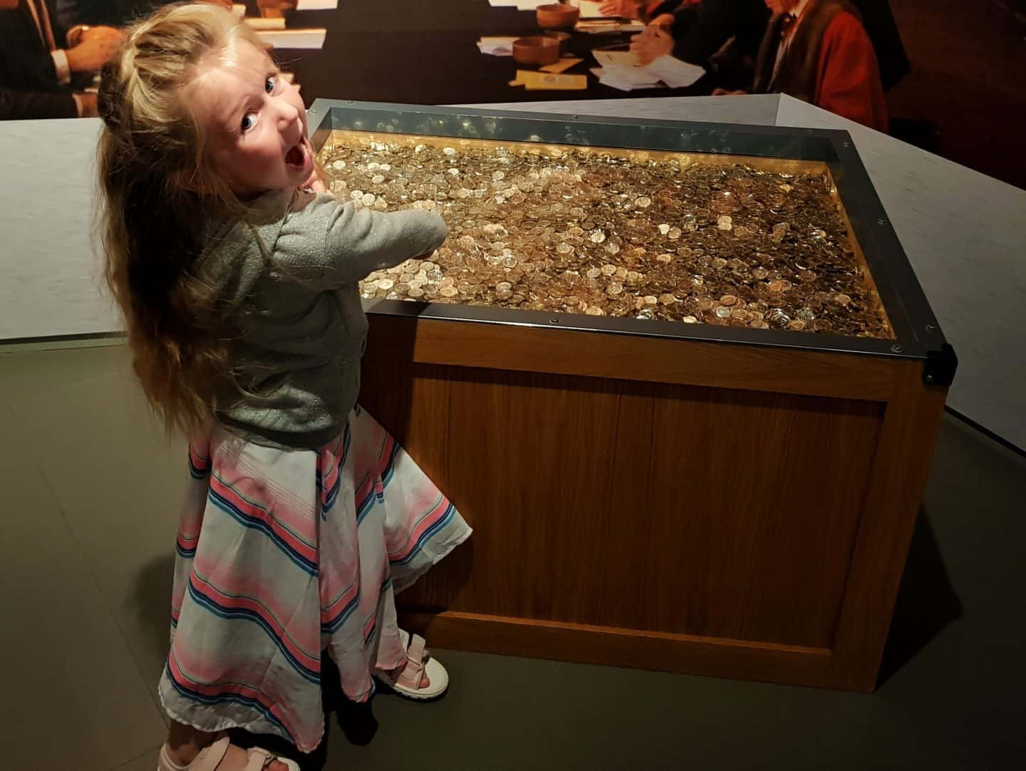 girl by display of pound coins at Royal Mint Experience