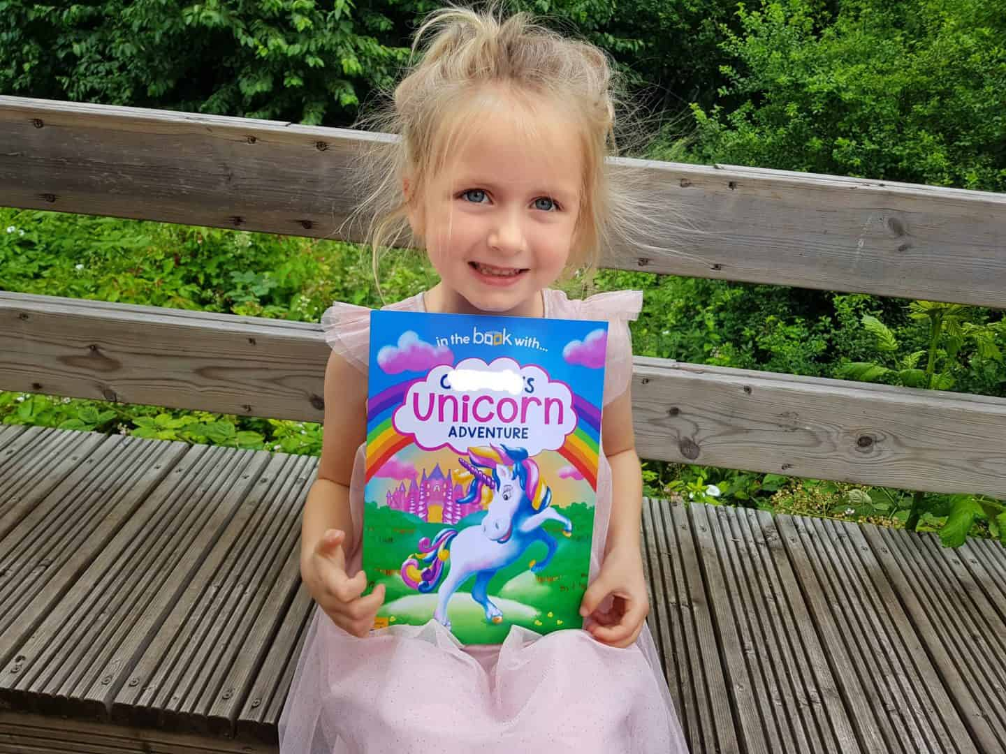 Child holding unicorn book