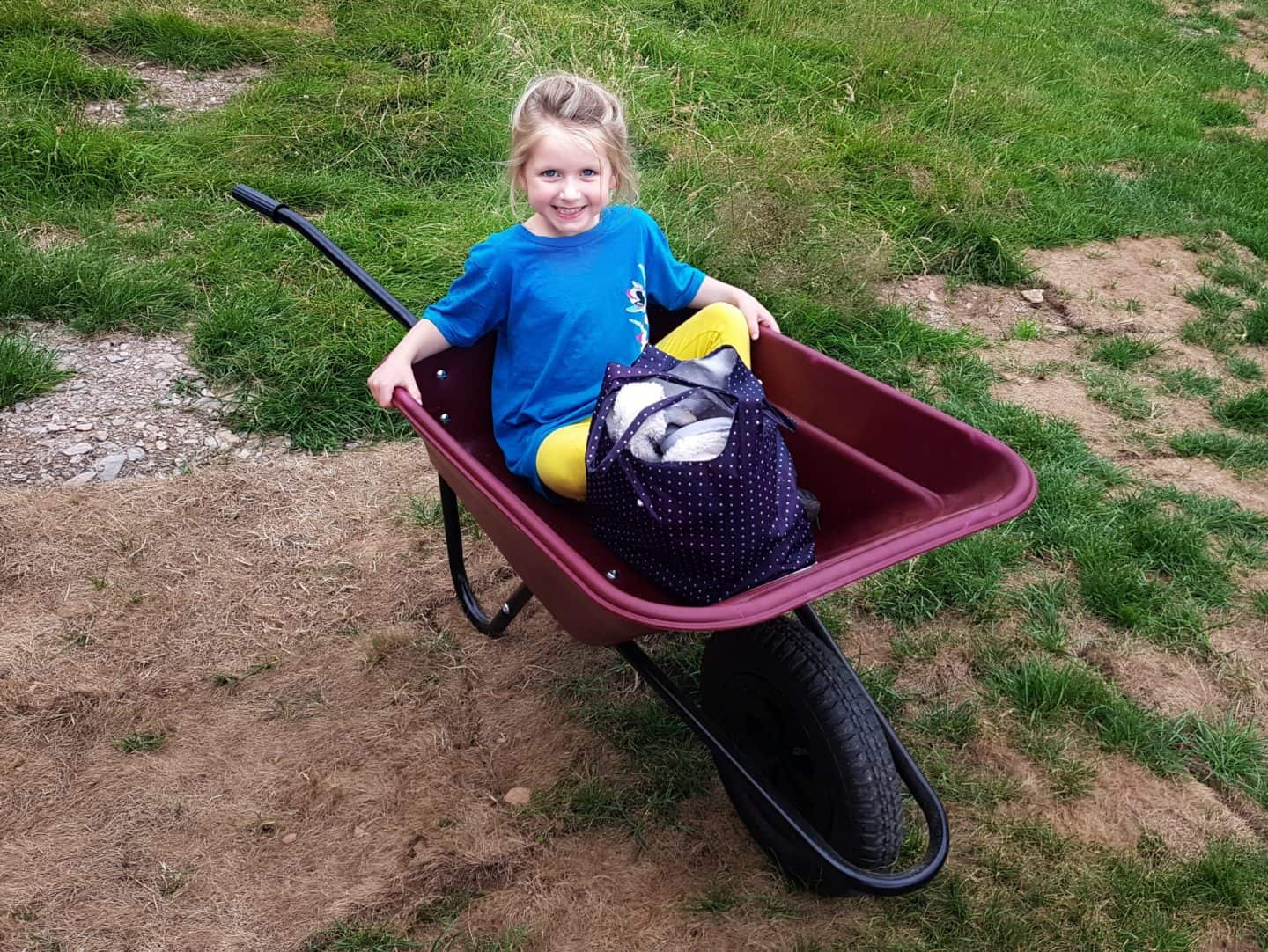 Girl in wheelbarrow at Feather Down glamping