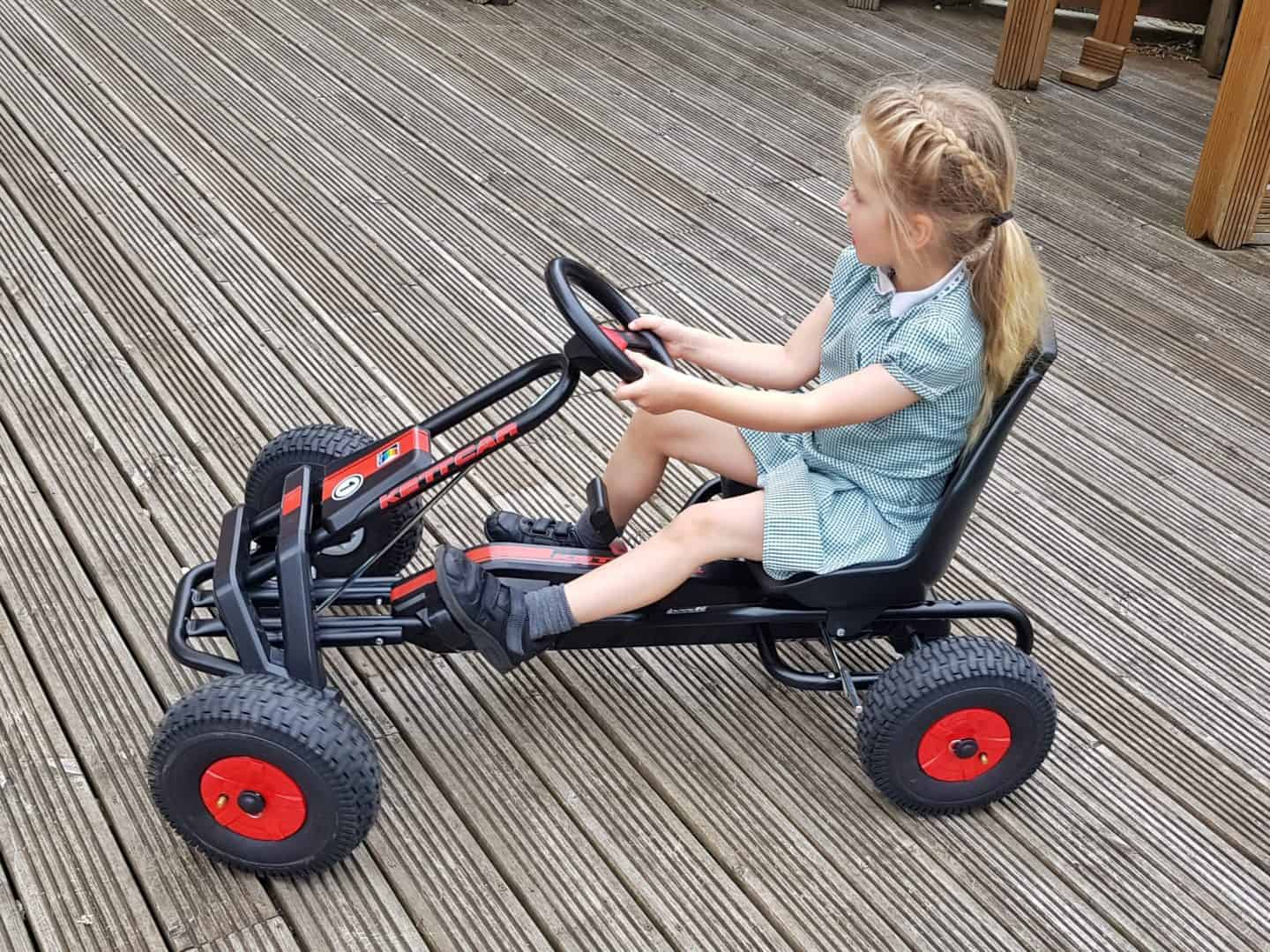 Girl riding Kettler Barcelona Air Go Kart side view on decking