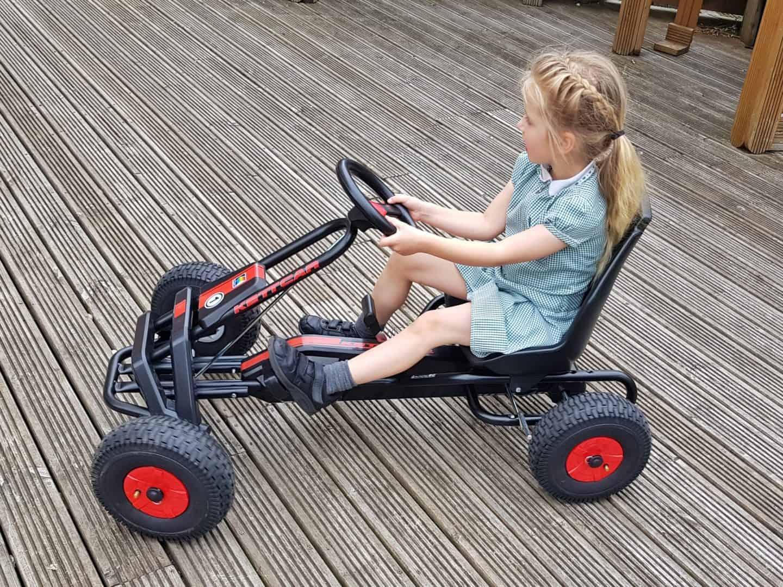 Girl riding Kettler Barcelona Air Go Kart side view on decking