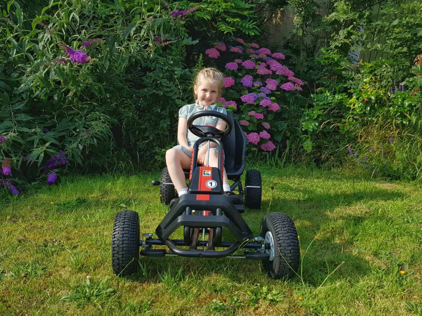 Girl riding Kettler Barcelona Air Go Kart on grass with flower bush behind