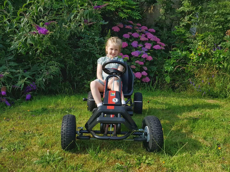 Girl riding Kettler Barcelona Air Go Kart on grass with flower bush behind