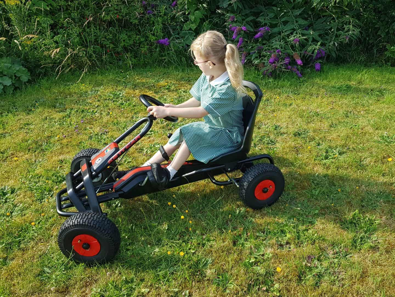 Girl riding Kettler Barcelona Air Go Kart side on view on grass
