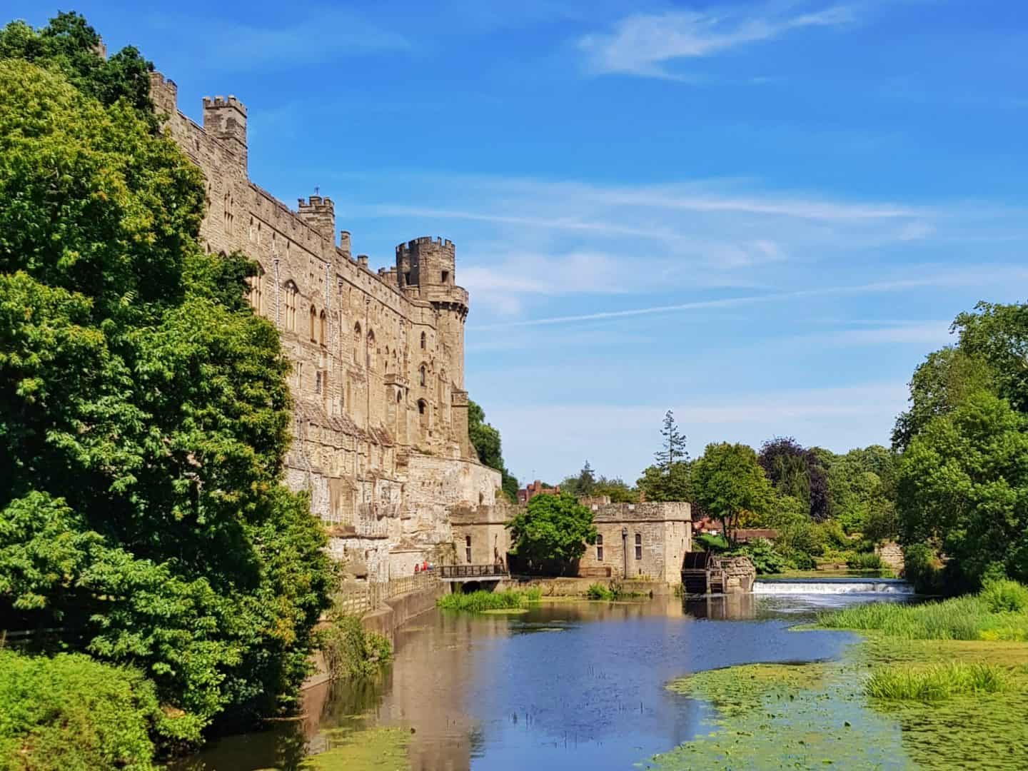 Warwick Castle viewed across the moat with waterfall on right hand side