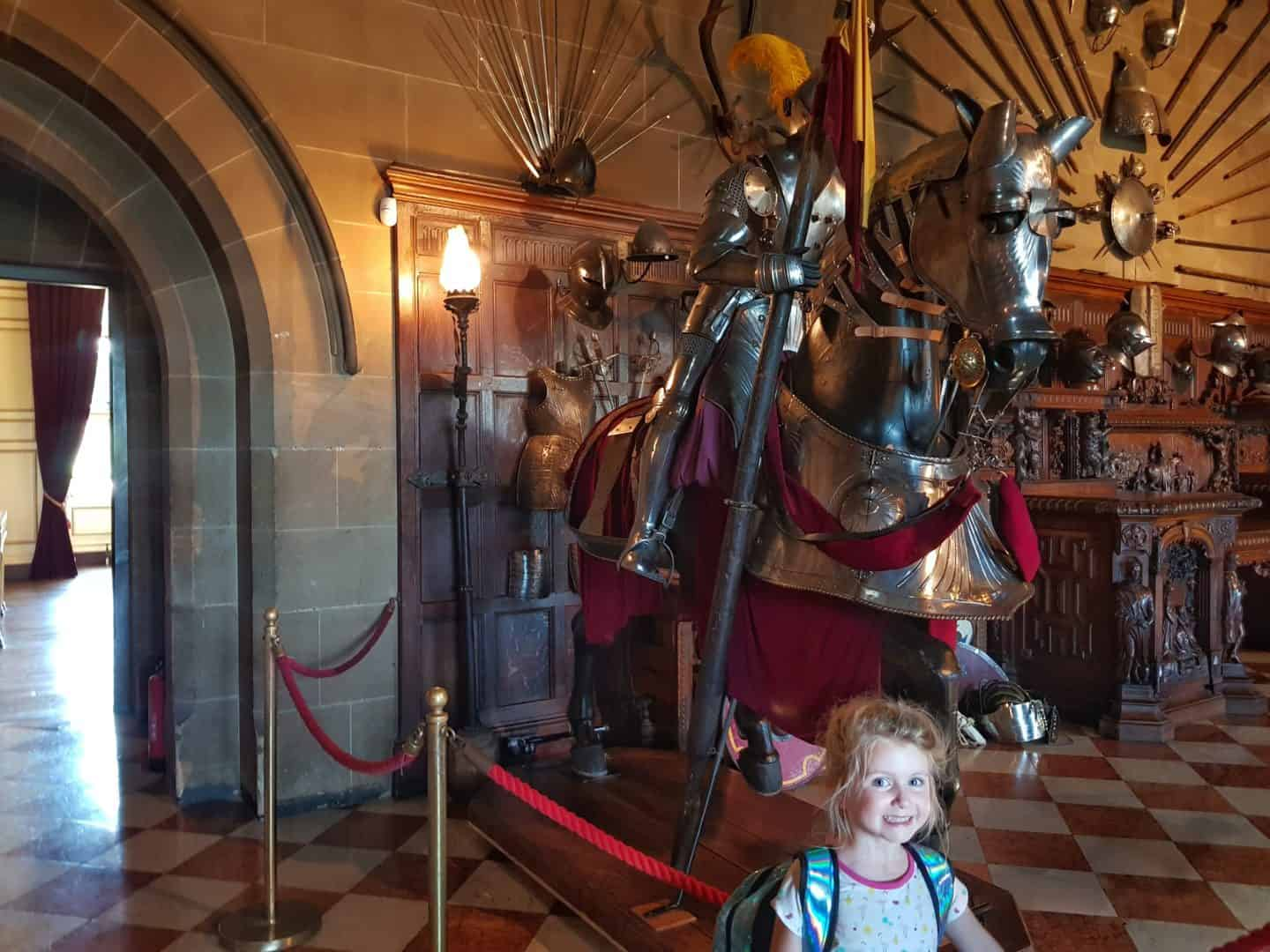 child with horse model in suit of armour in Warwick Castle Great Hall