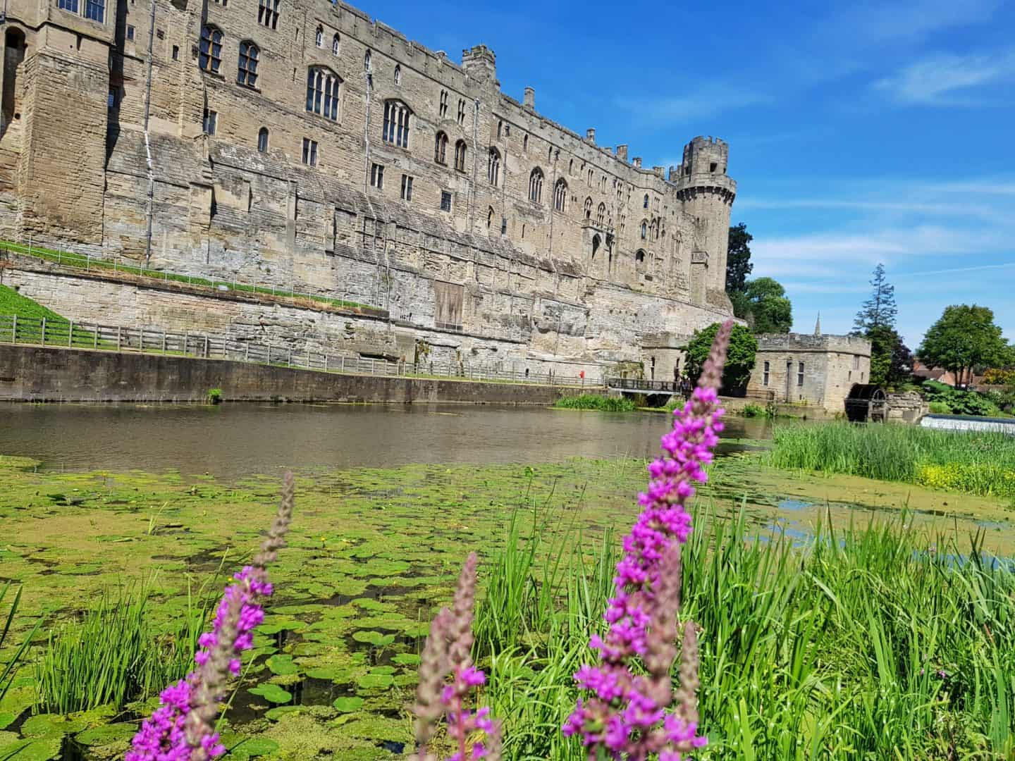 Warwick castle viewed across the moat with flowers in foreground