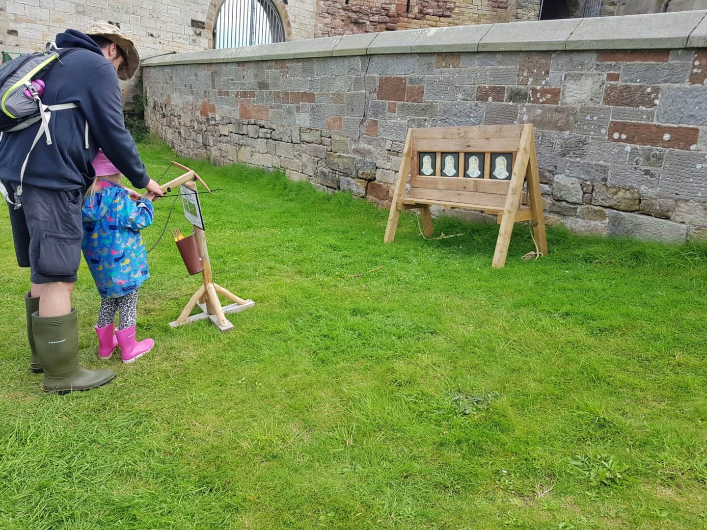 Child doing archery with a toy crossbow at Bamburgh Castle, helped by her dad