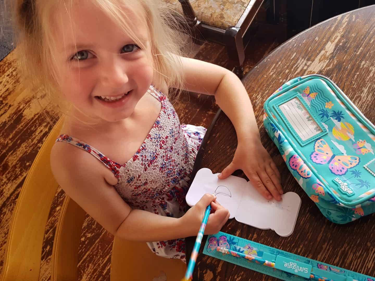 writing with Smiggle pencil and smiling