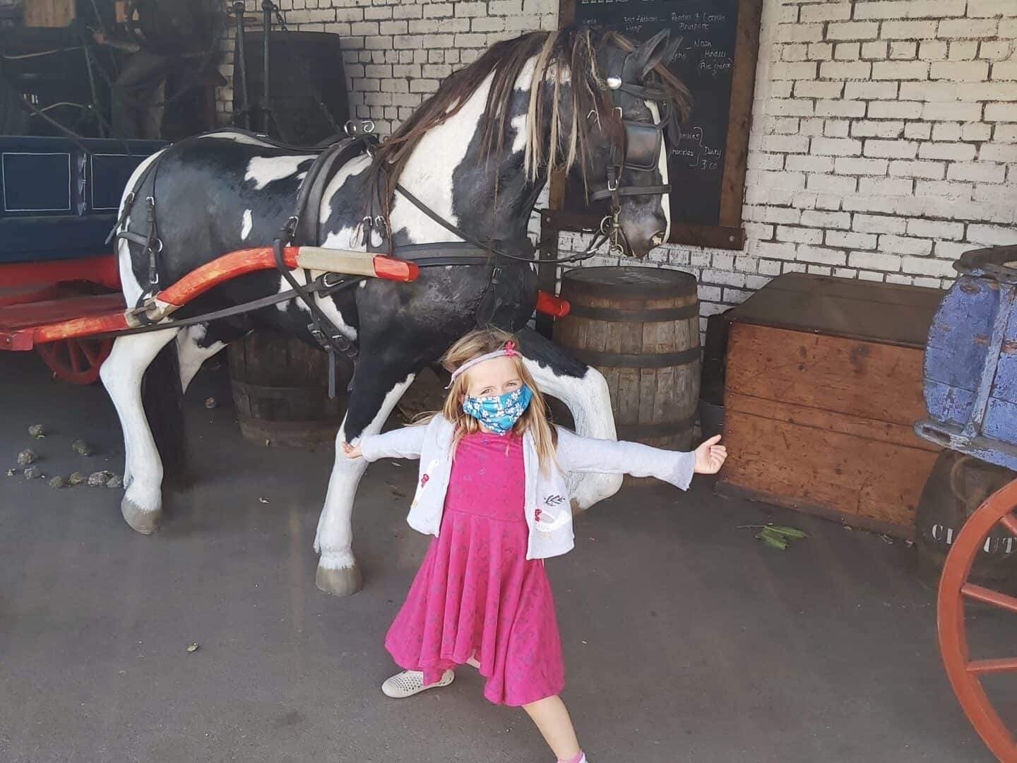 Girl wearing a mask in front of horse statue