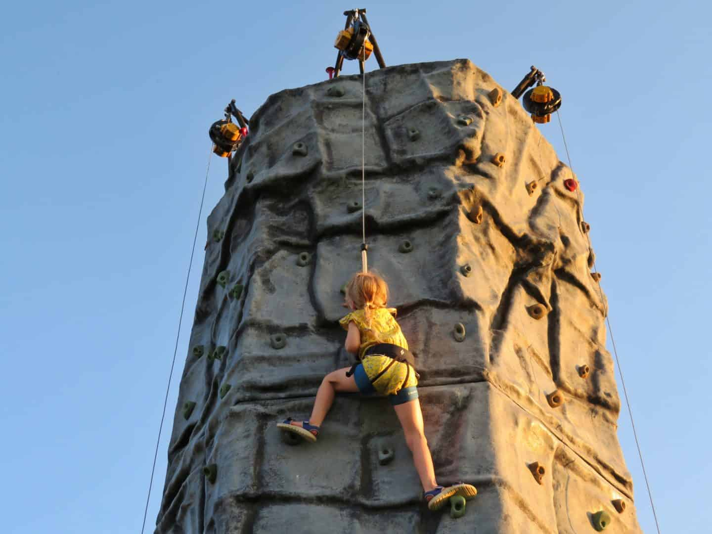 girl at top of climbing wall at sunshine festival 2019