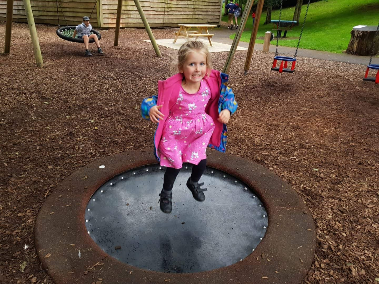 Little girl on trampoline in children's playground at Longleat Safari Park