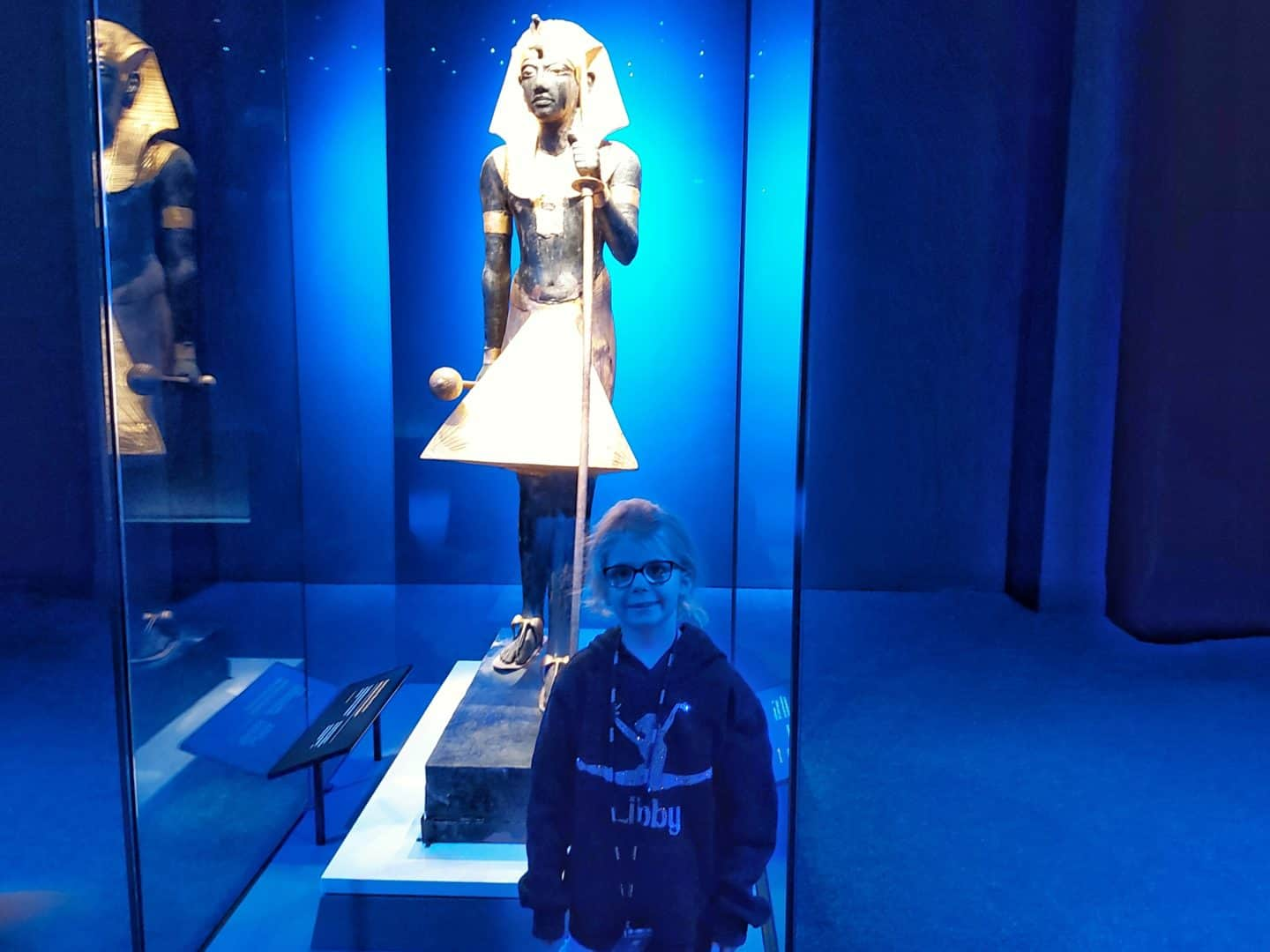 Little girl standing in front of a life sized guardian statue of Tutankhamun