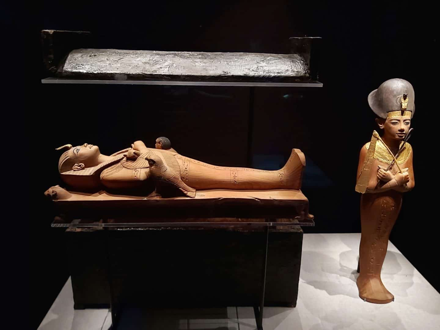 Two miniature statues. One is of Tutankhamun lying down as per the death mask. The other is standing up.