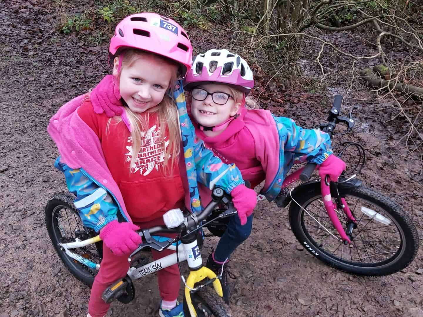 Two girls on bikes standing together on a muddy path at Westonbirt Arboretum