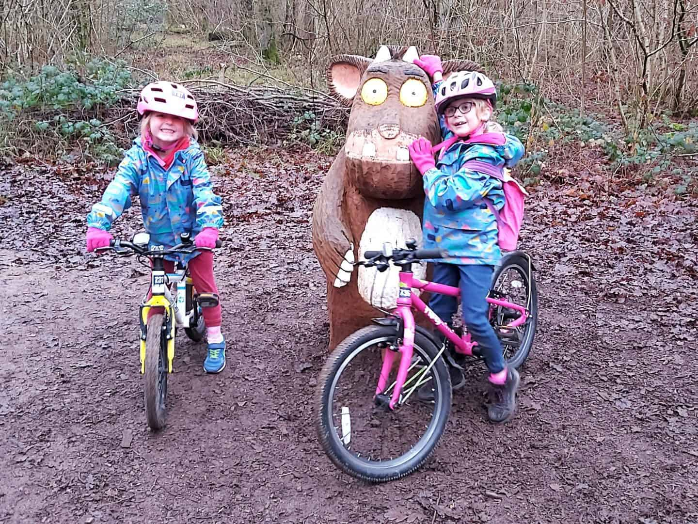 Two girls on bikes standing with the Gruffalo's child sculpture at Westonbirt Arboretum