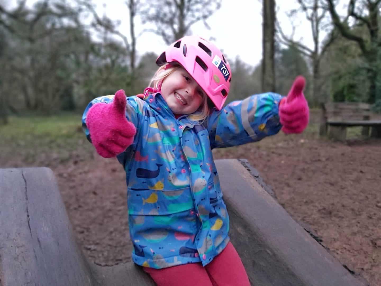 Girl in cycling helmet on log slide at Westonbirt Arboretum natural play area