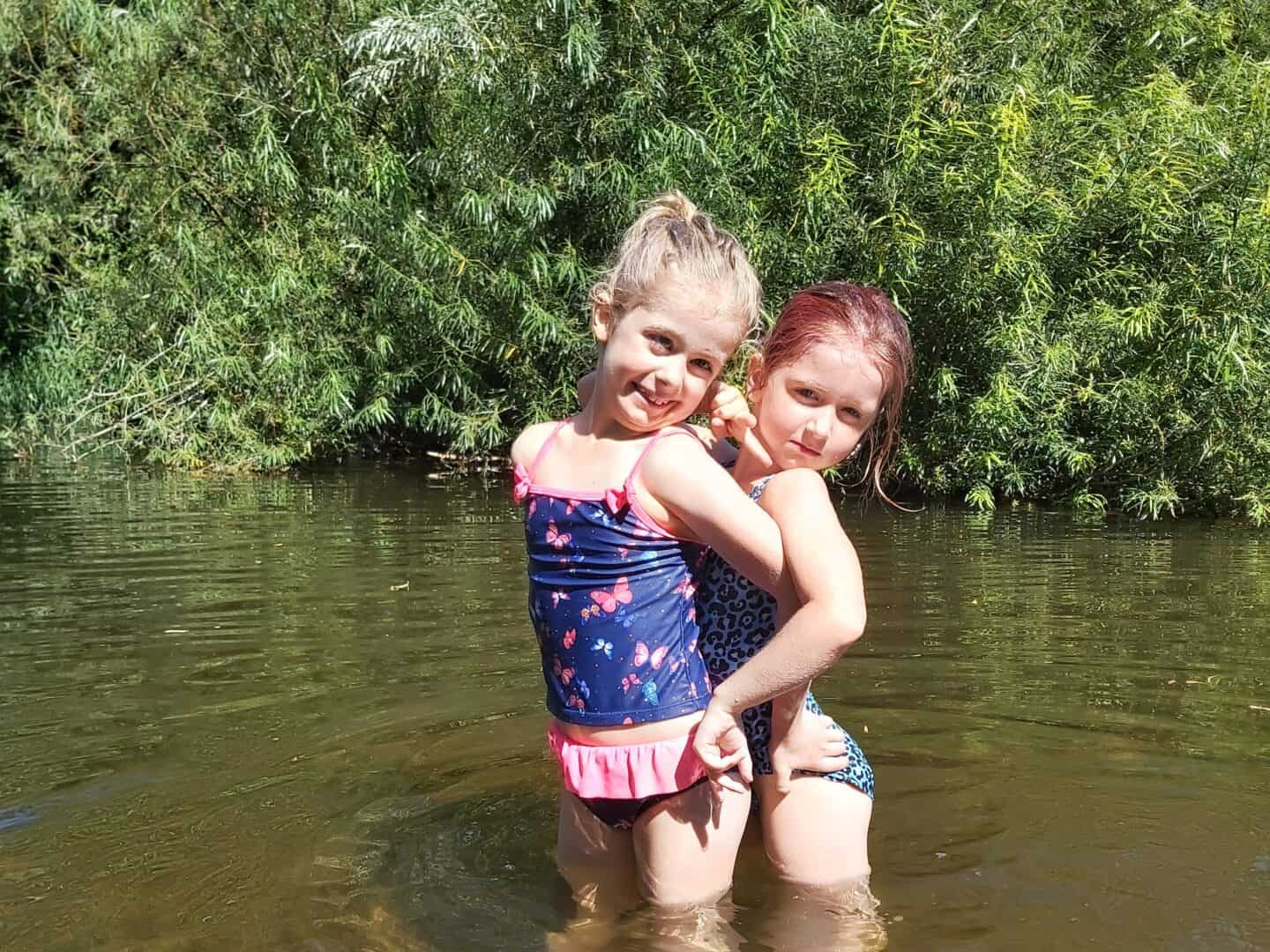 Two girls in swimming costumes standing in a river with a willow tree behind