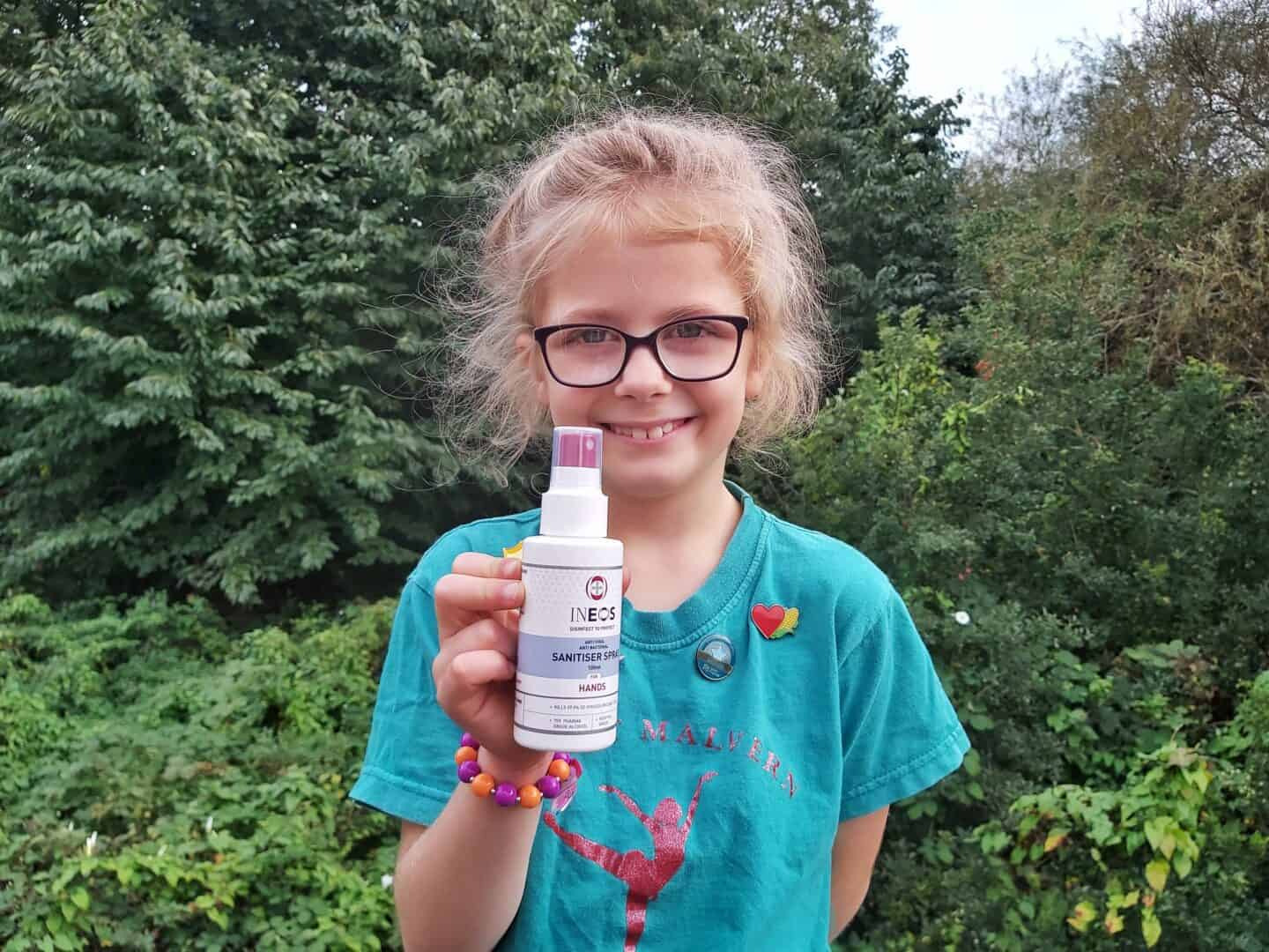 Girl holding Ineos Hygienics hand sanitiser spray. Nature reserve in background.