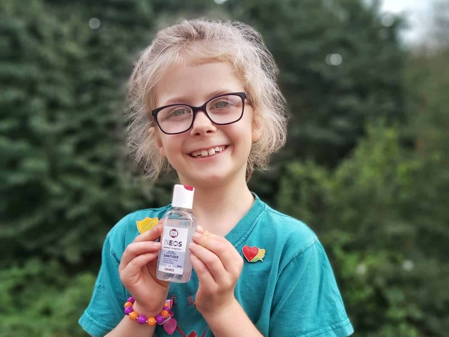 Girl holding miniature bottle of Ineos Hygienics hand sanitiser. Blurred background of trees.