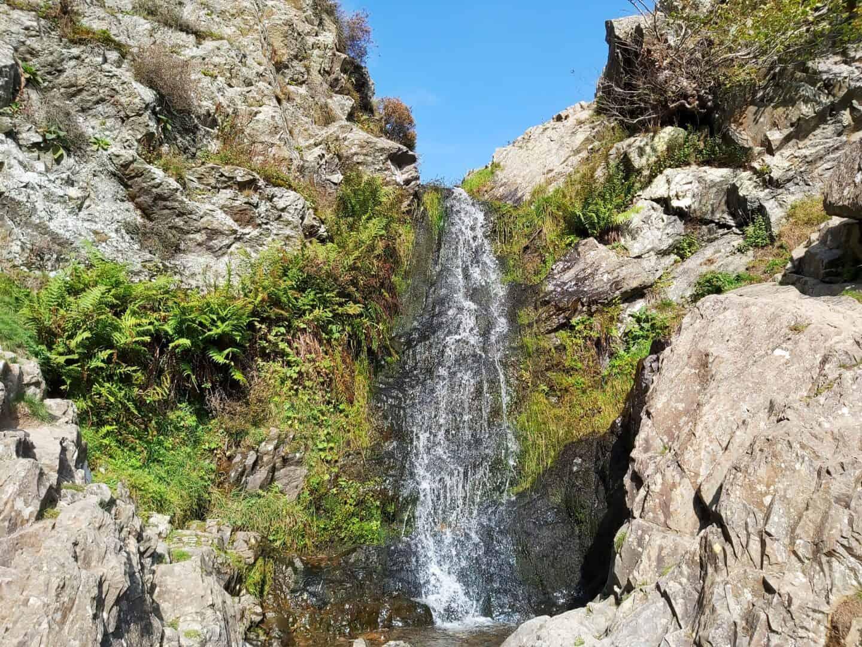Waterfall between rocks with blue sky behind