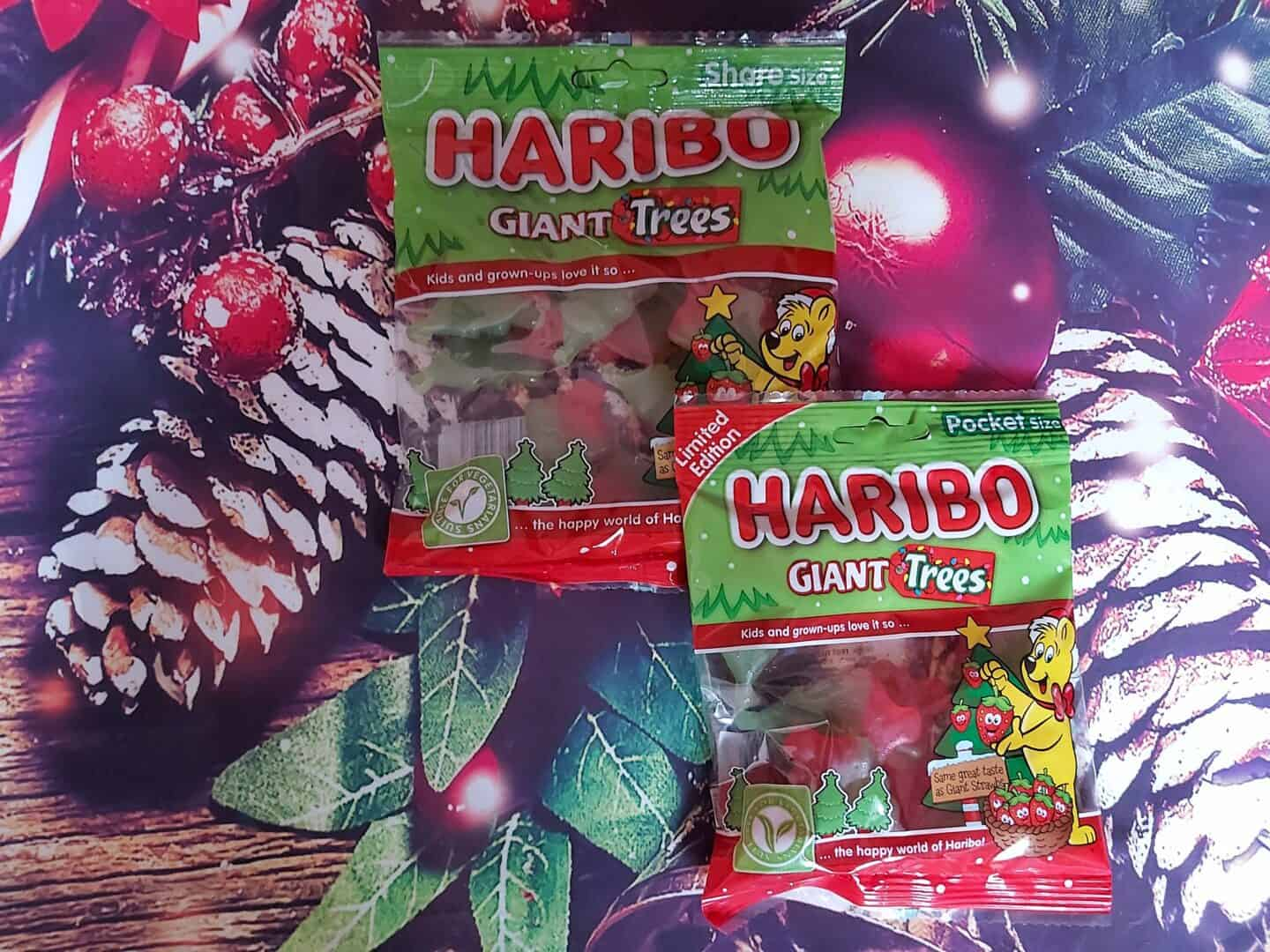 Two packets of Haribo Christmas trees against a festive background