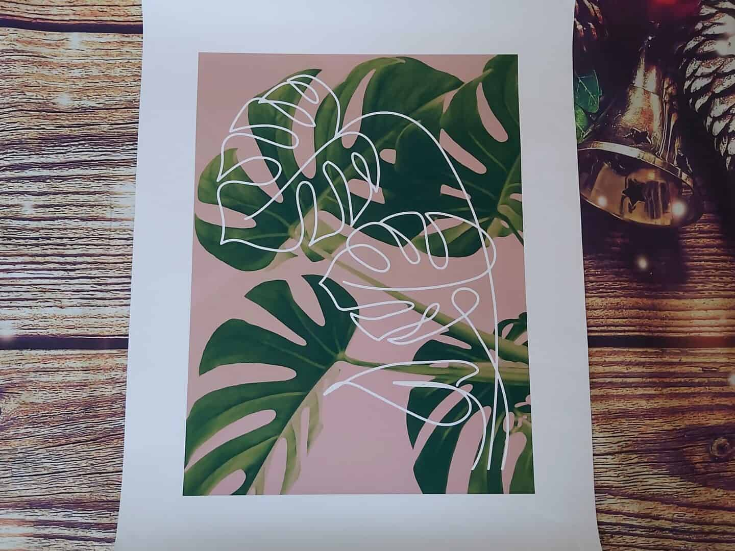 Floral print of green leaves on pink background