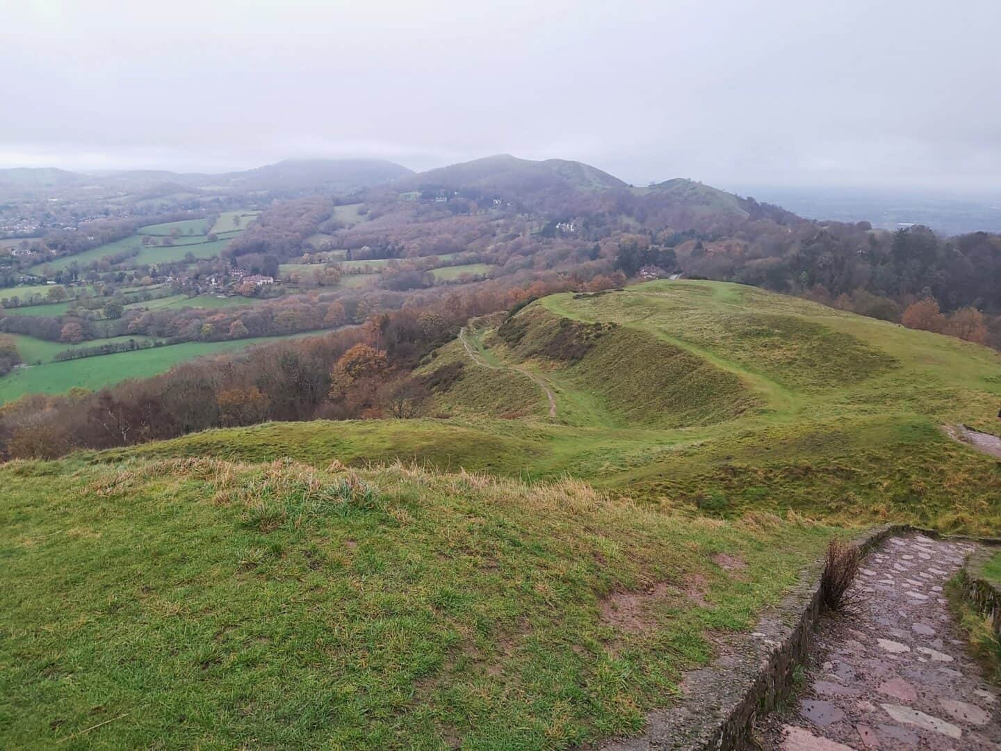 Path on right hand side leading down grassy hillside with Malvern Hills stretching from point of photo to the horizon