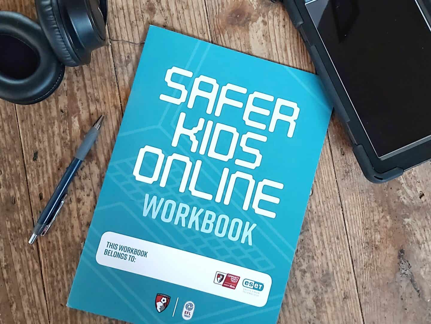 ESET Safer kids online workbook on wooden background with tablet, headphones and phone beside